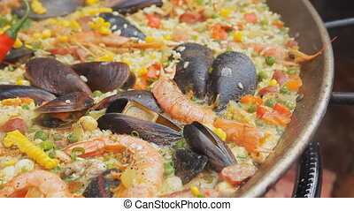 Spanish paella with yellow rice, shrimps and mussels cooking at the food market. Street food festival. Traditional spanish food. Rice with seafood boiling close up.
