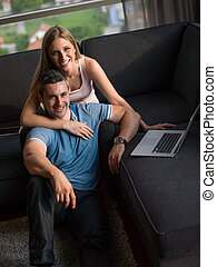 Attractive Couple Using A Laptop on couch - Attractive...