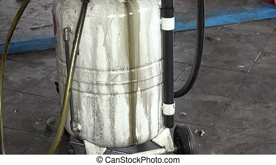 Used oil flow into car oil replacement equipment reservoir....