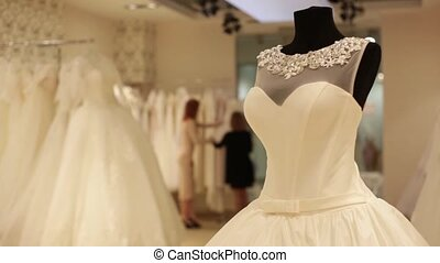 Close-up of dummy with wedding dress. shop assistant is...