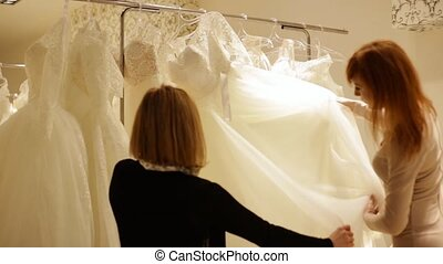 pretty young woman choosing a wedding dress. shop assistant...