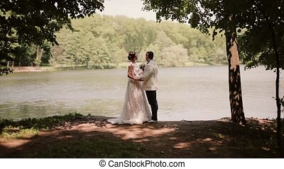 Lovers on a wedding day stand on a river bank looking at each other, kissing. Happy bride in a beautiful dress.