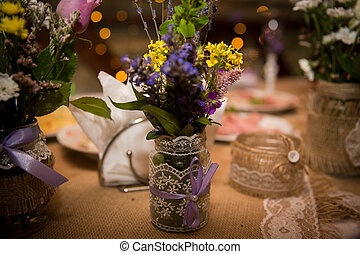 Beautiful bouquet of wild flowers in the designer jar for a wedding celebration. Handmade. Close-up.