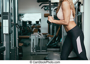 Triceps pull down exercising - Woman doing triceps exercise...