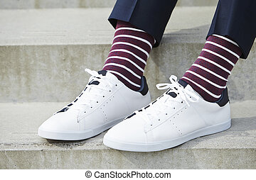 Stripy socks and white sneaker on guy, close up