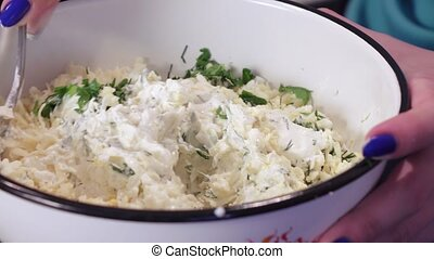 Preparation of salad from greens and cheese - Adding sour...