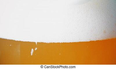 White foam sliding down of beer glass. UltraHD video - White...