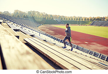 happy young man running upstairs on stadium - fitness,...