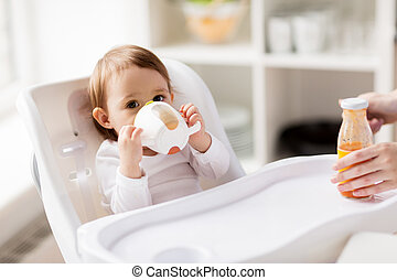 baby drinking from spout cup in highchair at home -...