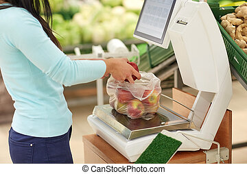 woman weighing apples on scale at grocery store - shopping,...