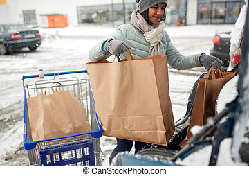 woman loading food from shopping cart to car trunk -...