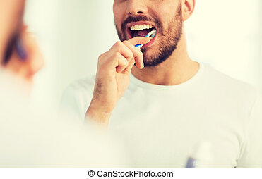 close up of man with toothbrush cleaning teeth - health...