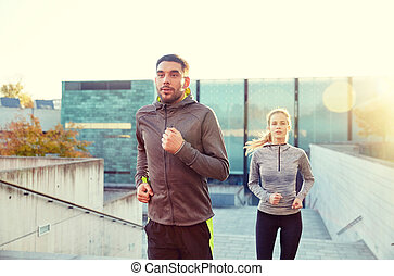 happy couple running upstairs on city stairs - fitness,...