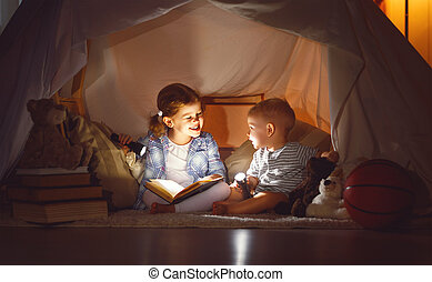 children boy and girl reading book with  flashlight in  tent