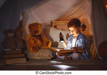 child girl with a book and a flashlight and teddy bear...