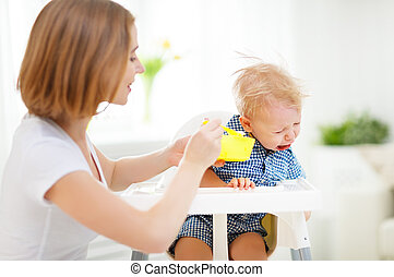 mother feeds the cry baby son with a spoon