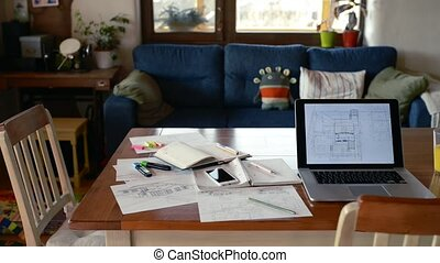 Home office. Table with laptop, house plans and notebook....