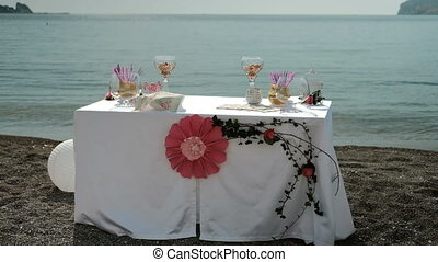 On the coast there is a table with a flower for a romantic...