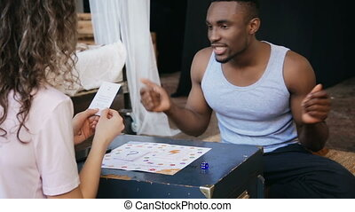 Multiethnic couple sitting on the floor and playing the board game. Man dance while woman makes the task in card.