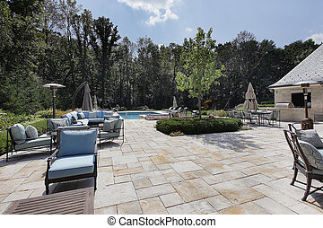 Large stone patio with swimming pool
