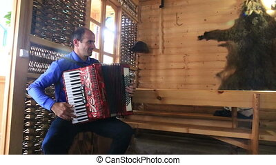 Man playing accordion at traditional interior