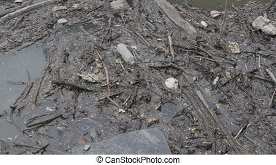 Garbage in the river - Garbage including water bottles in...