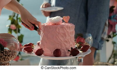 Woman cuts off a piece of pink cake and give the man a...