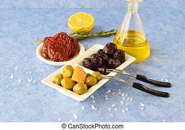A set of dishes of greek cuisine: olives, sun dried tomatoes, lemon, glass jar with olive oil. Traditional Greek food. Mediterranean lifestyle