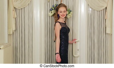 Girl ready to go to prom. Young girl in evening dress waves...