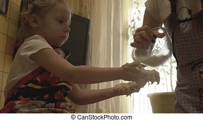 Mom sprinkles the hand of his daughter flour