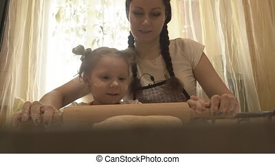 Mom with a girl with a rolling pin roll the dough - Mom with...