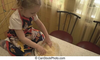 A small child sits on the table and knead the dough