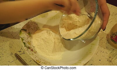 From the bowl children's hand pours the flour