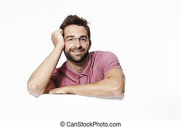 Confident chap leaning in white studio