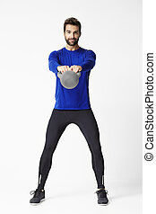 The kettle bell kid - Man lifting kettle bell in studio,...