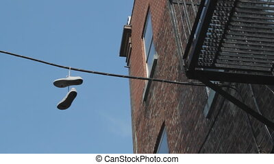 Sneakers hanging from wire - A pair of sneakers hanging from...