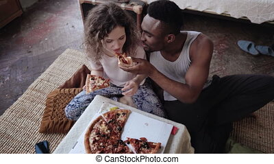 Happy multiethnic couple sitting on the flow, hugging and eating fast food. Woman feed the hungry man a slice of pizza.