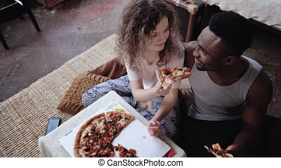 Woman offers pizza to man, but eat slice by herself....