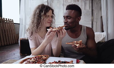 Multiracial couple have fun during the meal. Woman feed the...