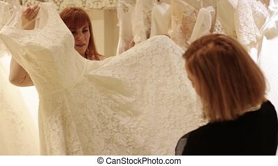 shop assistant helping for beautiful young woman choosing a wedding dress in a wedding shop