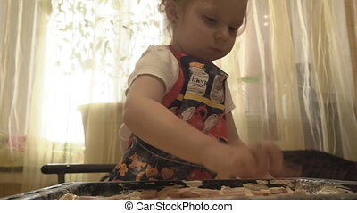 The child puts on the pan sausage pizza