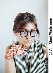Beautiful girl in white room, with mehendi on a hand -...