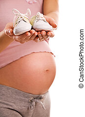 Pregnant woman holding pair of white shoes for baby (Shallow...