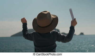 Small boy actively waving hands, calling his parents from...