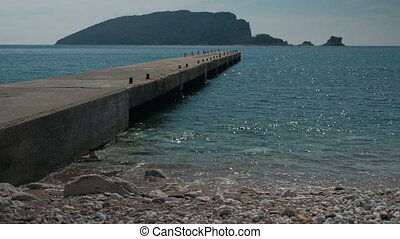 A long pier stretches to the sea with mountains in sunny...