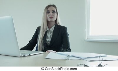 Young beautiful blonde is thinking in the office at the table in front of the laptop.