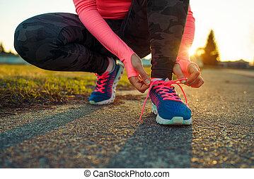 Running shoes - woman tying shoe laces. Closeup of female...