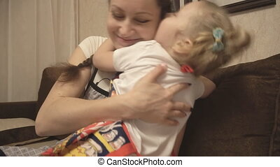 Mother hugging her daughter in the apron - Mother hugging...