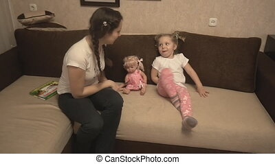 Mother and daughter playing on the sofa and carpet bully -...