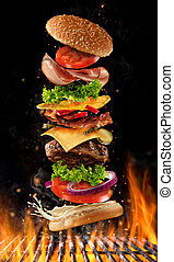 Flying burger ingredients above grill fire. Concept of low...